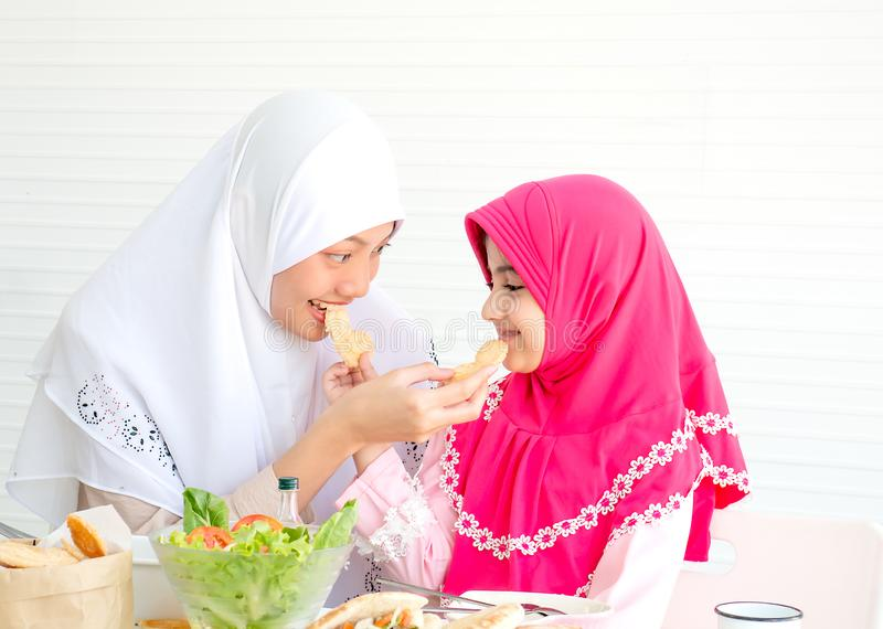 Muslim mother and her daughter are eating cookies together with a bowl of vegetable salad on white background royalty free stock photo