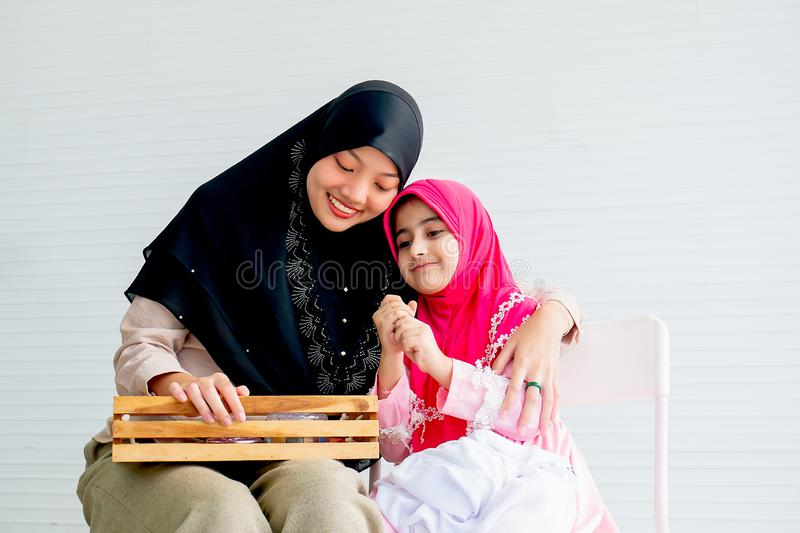 Muslim mother and her daughter are enjoin with cosmetic activity together in the room with white background and copy space stock photography