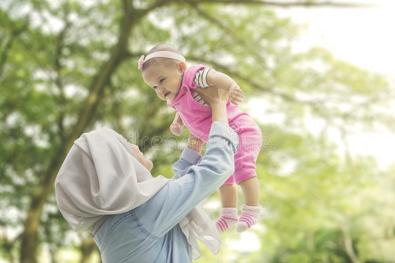Muslim mother playing with daughter at park stock photos