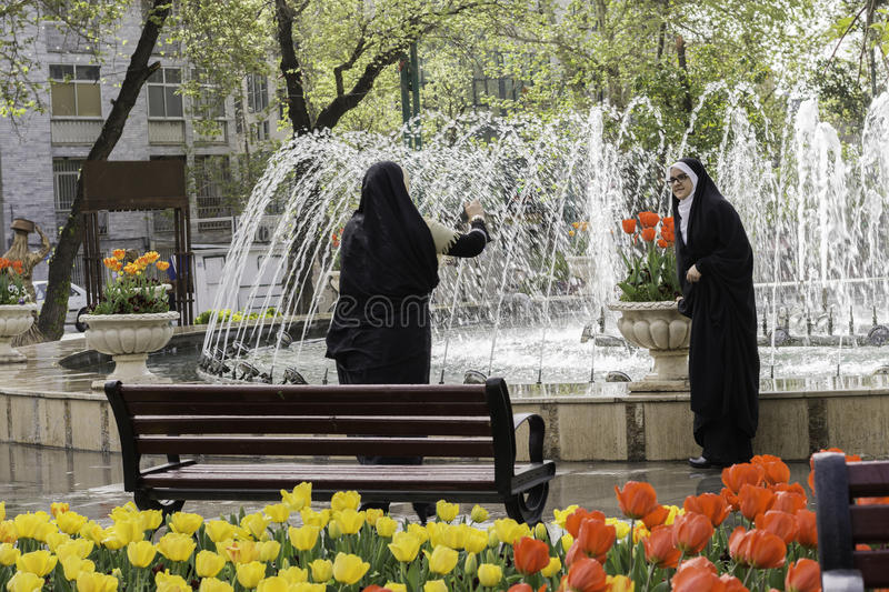 Muslim mother taking a photograph of her daughter by cellphone a stock images