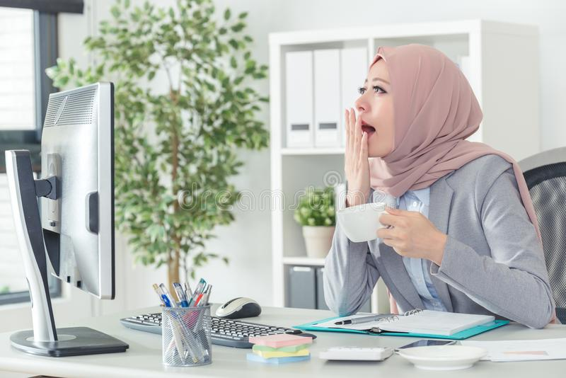 Muslim office lady yawning, working at office job. Muslim office lady holding coffee and yawning, wants to take a break. Bored woman working at office job. Tired stock photography