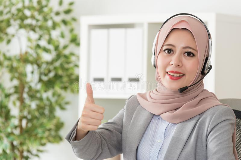 Muslim office worker doing online service work. Happy friendly muslim woman office worker doing online service work and wearing headphone showing thumb up royalty free stock photography