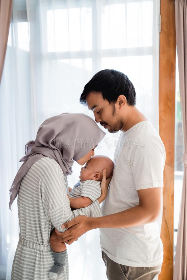 Muslim Parents Kiss Their Baby Stock Image