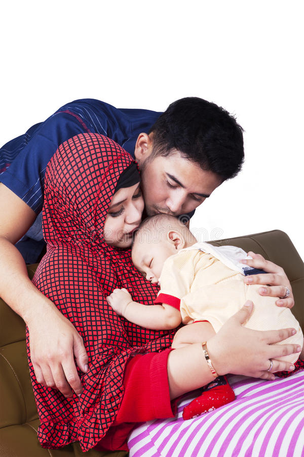Muslim parents kiss their baby. Portrait of two muslim parents kiss their baby boy while sleeping on the mother's chest royalty free stock images