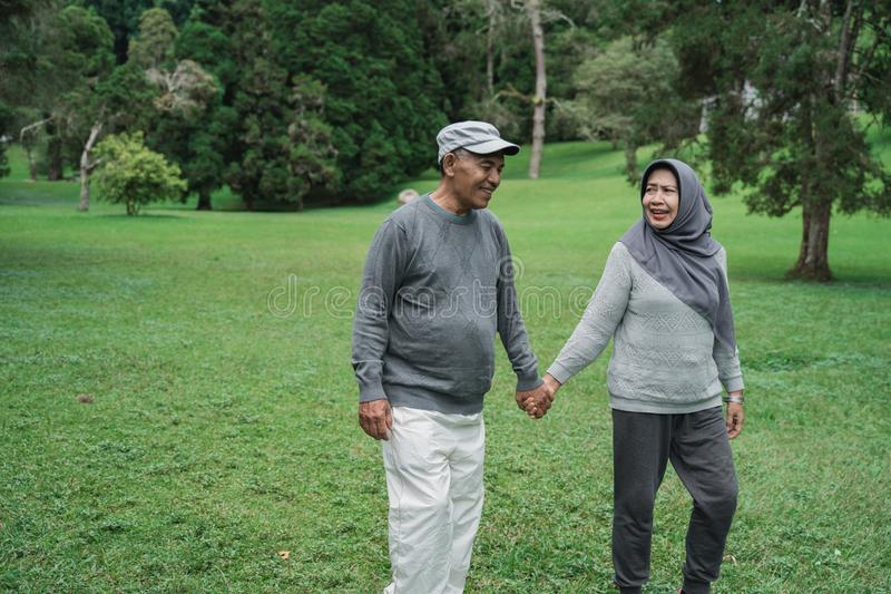 Muslim senior couple walking in the garden together stock photography