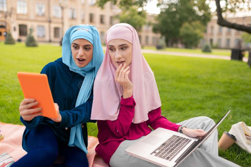 Muslim students feeling surprised after reading info in the Internet. Surprised after reading. Muslim students wearing hijabs feeling surprised after reading royalty free stock photo