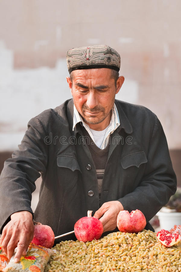 Muslim vendor sells grapes on the street, Weihai, China. WEIHAI–NOV. 30, 2006. Muslim vendor sells grapes. When they settle in cities, many migrants royalty free stock images