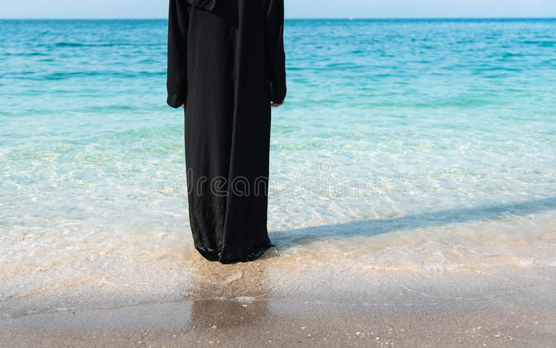 Muslim woman in abaya by the seaside. Muslim woman in abaya spending time by the seaside, beach, summer, hijab, water, vacation, covered, rear, copy, space stock photos