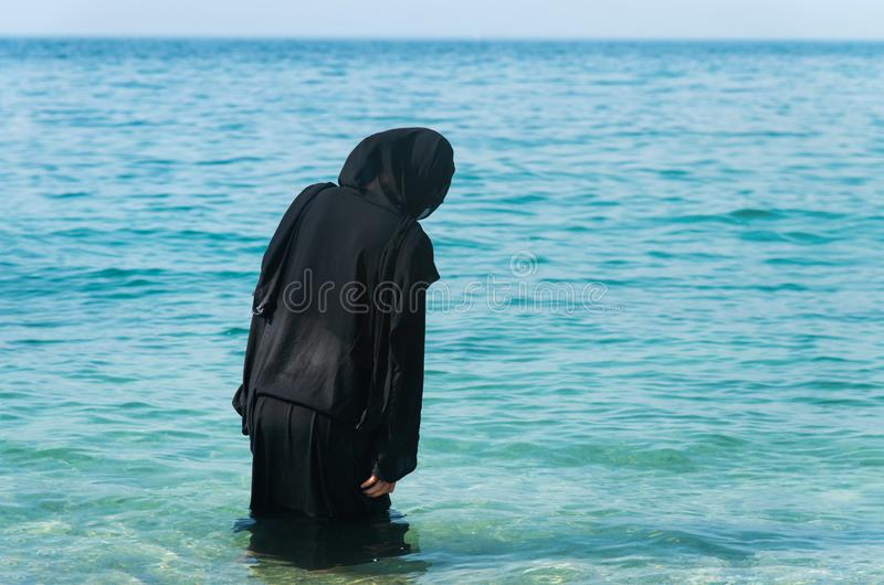 Muslim woman in abaya by the seaside. Muslim woman in abaya spending time by the seaside, beach, swimming, summer, hijab, wet, water, vacation, covered, rear royalty free stock photos
