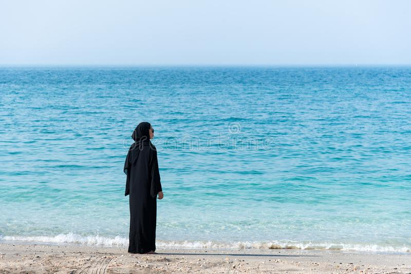 Muslim woman in abaya by the seaside. Muslim woman in abaya spending time by the seaside, beach, summer, hijab, water, vacation, covered, rear, copy, space royalty free stock photo