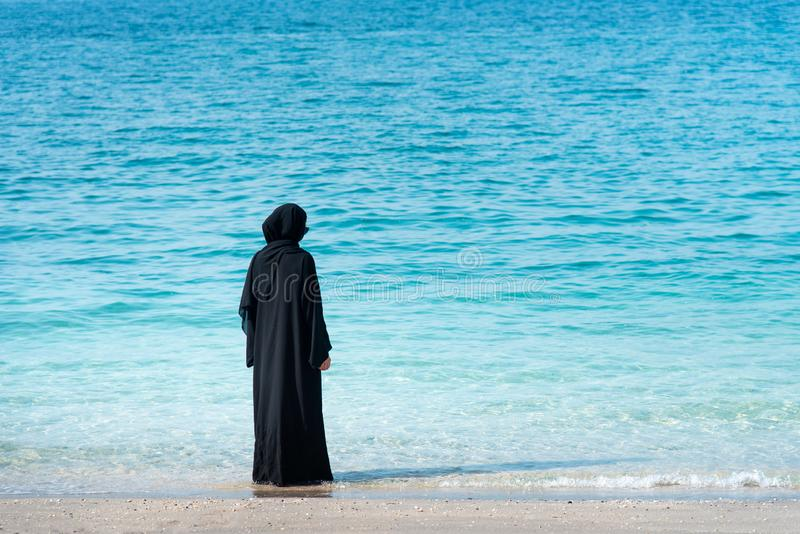 Muslim woman in abaya by the seaside. Muslim woman in abaya spending time by the seaside, beach, summer, hijab, water, vacation, covered, rear, copy, space stock image