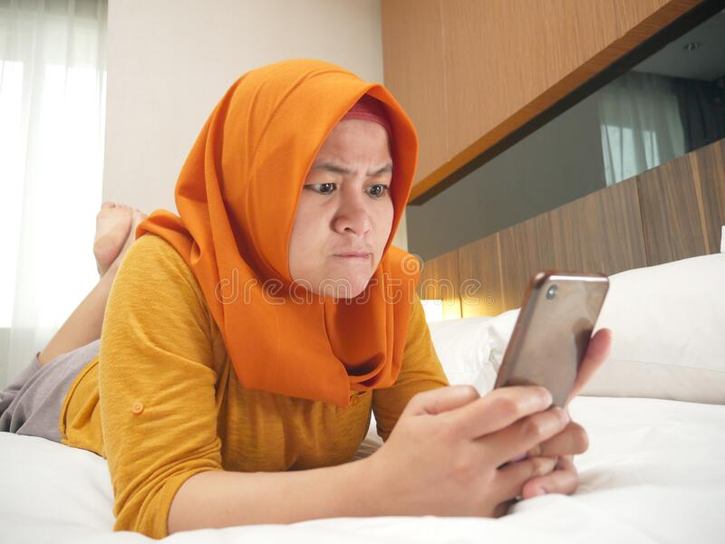 Muslim Woman Angry While Reading Text Message on Smart Phone. Portrait of beautiful young Asian muslim woman angry when reading bad news text message on her stock photo
