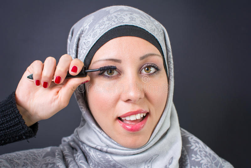 Muslim woman applying mascara royalty free stock photography