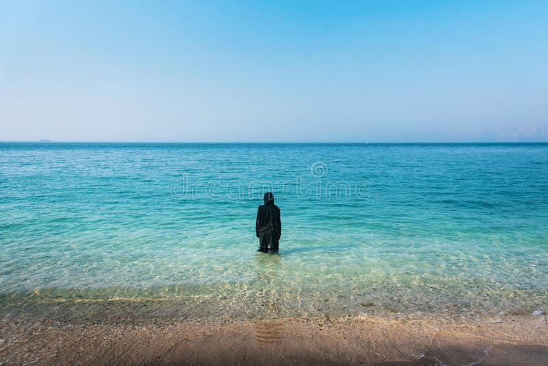 Muslim woman on the beach back view. Muslim woman in abaya on the beach back view, seaside, swimming, summer, hijab, wet, water, vacation, covered, rear, copy stock photo