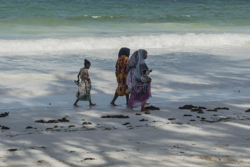 Muslim Woman on the beach. Women with colorful clothes wolking at Beach in Kiwengwa Village near the Kiwenga beach resort hotel , Zanzibar , Tanzania . Africa royalty free stock photo