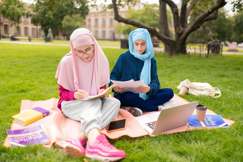 Dark-eyed muslim woman wearing hijab sitting outside royalty free stock image