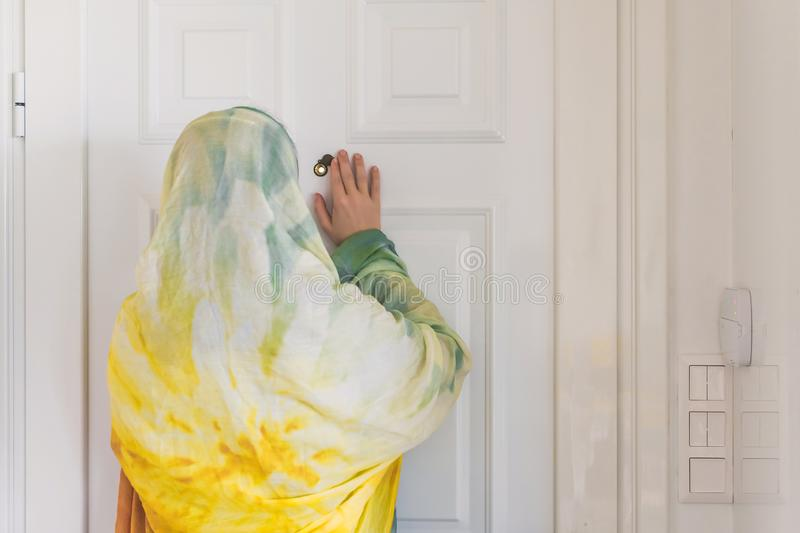 Muslim woman in a colorful scarf looking on peephole door. When somebody rings the doorbell royalty free stock photo