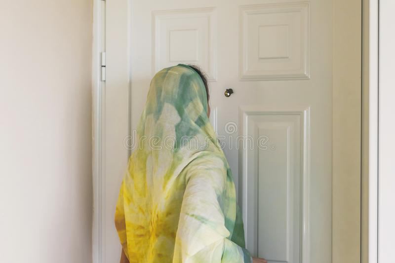 Muslim woman in a colorful scarf looking on peephole door. When somebody rings the doorbell stock images