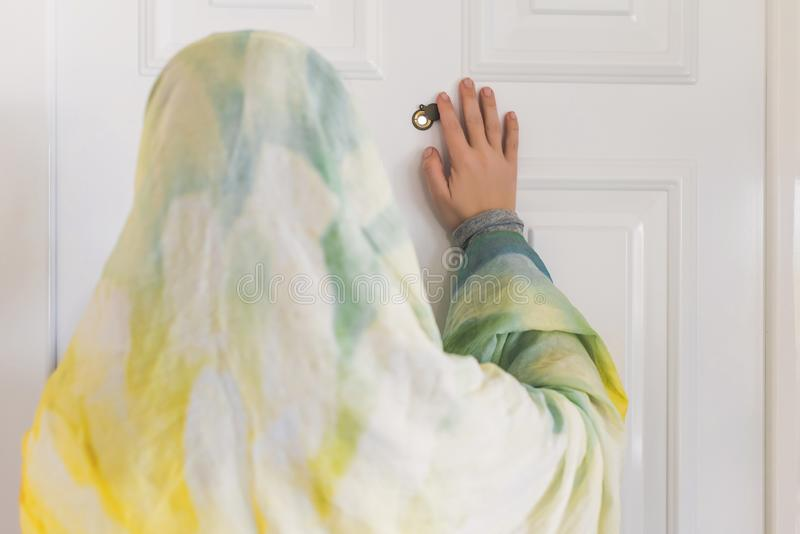 Muslim woman in a colorful scarf looking on peephole door. When somebody rings the doorbell royalty free stock images