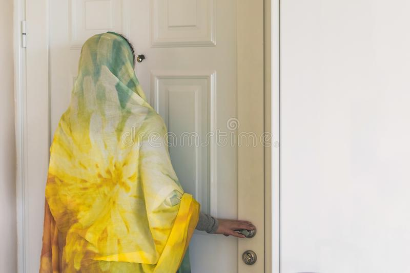 Muslim woman in a colorful scarf looking on peephole door. When somebody rings the doorbell stock photo