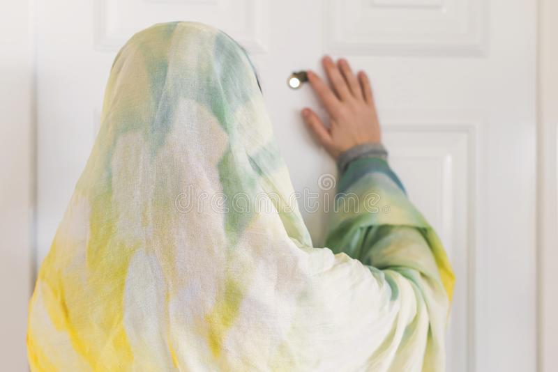 Muslim woman in a colorful scarf looking on peephole door. When somebody rings the doorbell royalty free stock photography
