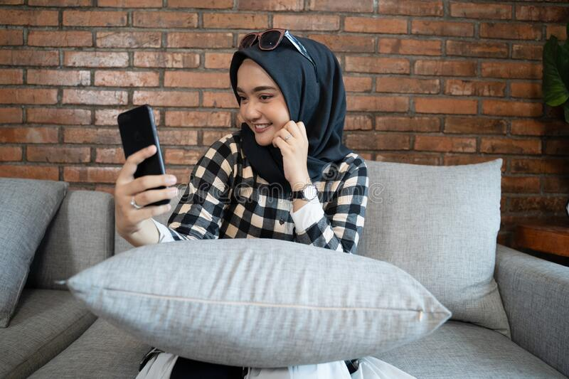Muslim woman conference call. Using smart phone stock photo