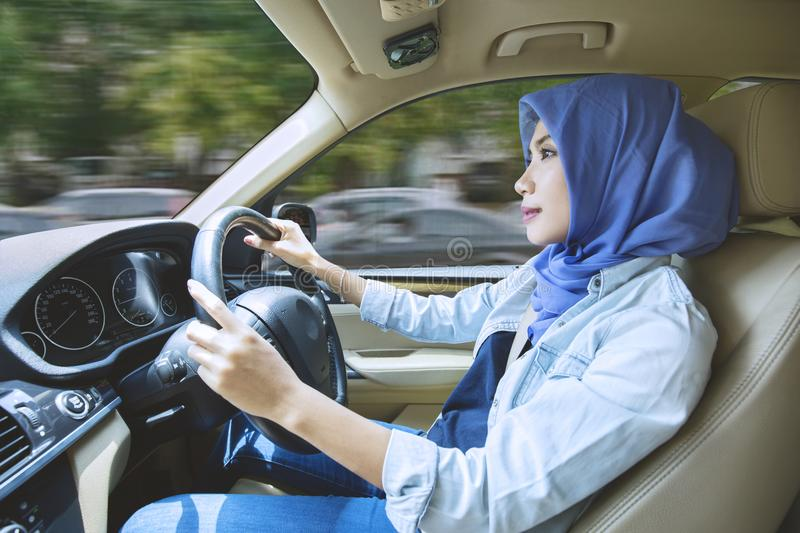Muslim woman driving a car on the road stock photo
