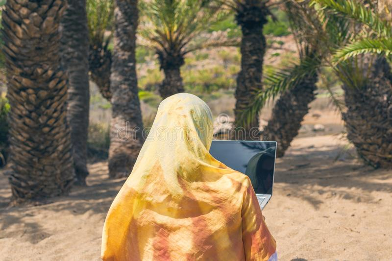 Muslim woman freelancer in a colorful scarf with laptop sits on the beach. Dubai. Halal travel. stock image