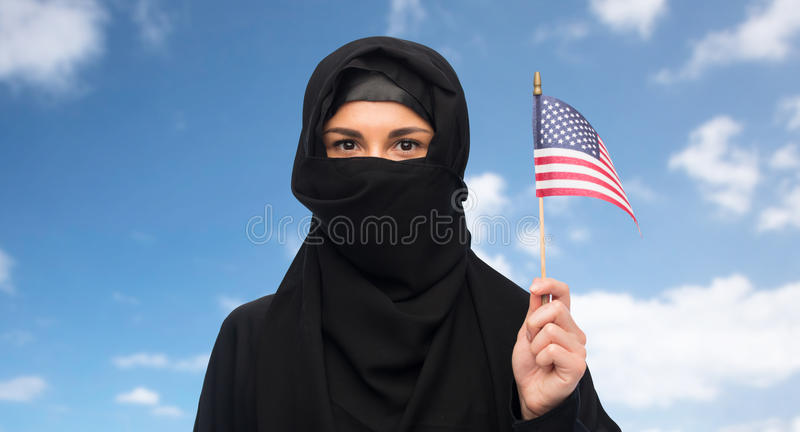 Muslim woman in hijab with american flag. Immigration and people concept - muslim woman in hijab with american flag over blue sky and clouds background royalty free stock images
