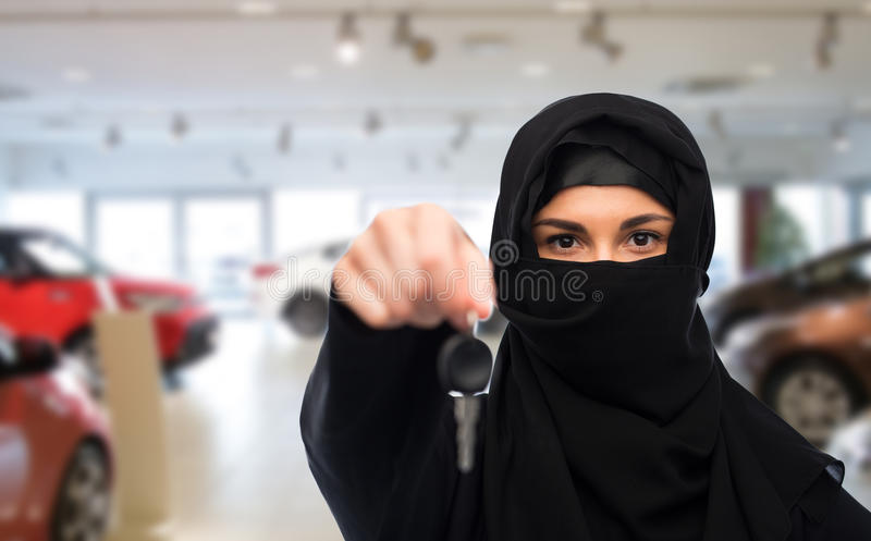Muslim woman in hijab with car key over car show. Property and people concept - muslim woman in hijab with car key over car show background stock images