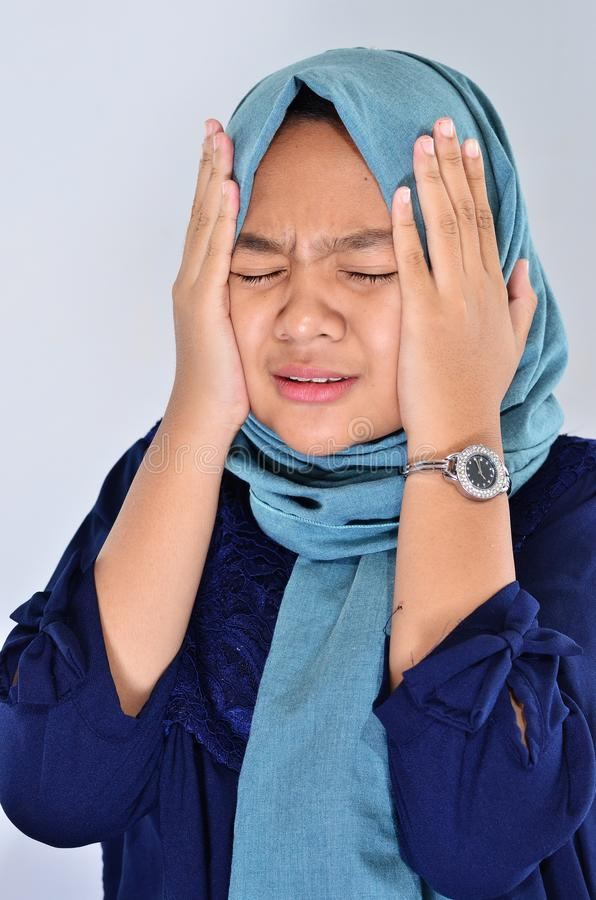 A Muslim woman in a hijab cries with holding her face using her hands. Asian girl is depressed, sad. Close-up image. In gray background stock images