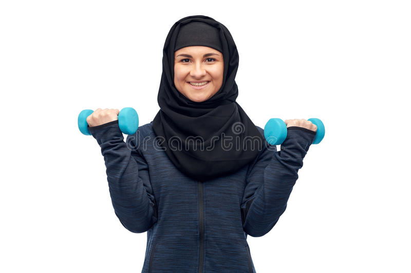 Muslim woman in hijab with dumbbells doing fitness. Sport, fitness and people concept - happy muslim woman in hijab with dumbbells doing exercises stock photography