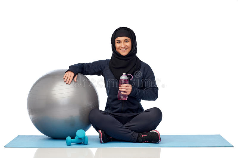 Muslim woman in hijab with fitness ball and bottle. Sport, fitness and people concept - happy smiling muslim woman in hijab with exercise ball, dumbbells and stock images