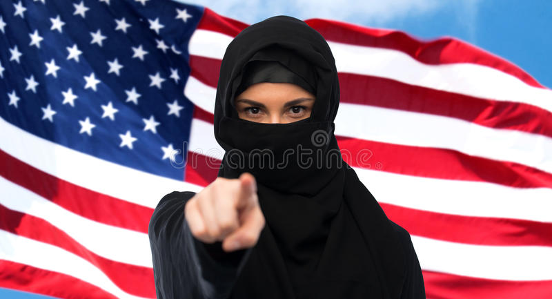 Muslim woman in hijab pointing finger to you. Immigration and people concept - muslim woman in hijab pointing finger to you over american flagbackground stock photos