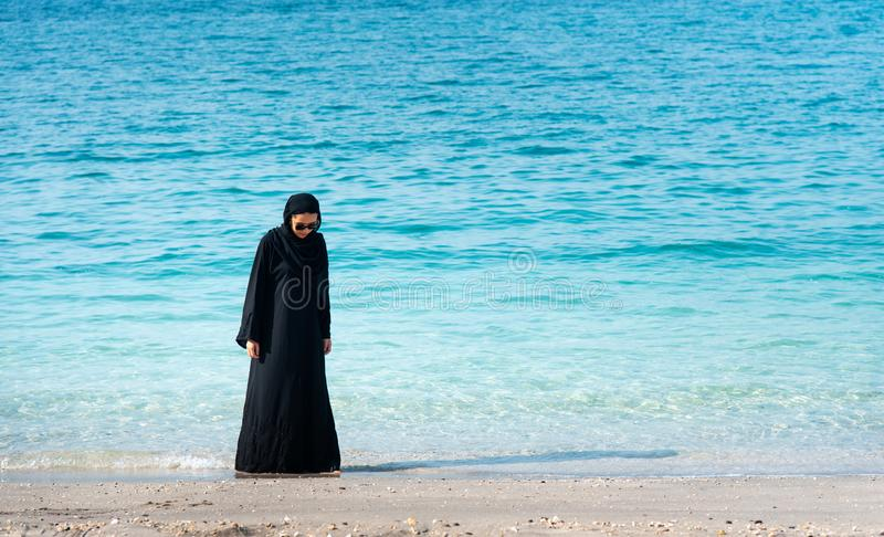 Muslim woman in hijab by the seaside. Muslim woman in hijab spending time by the seaside, beach, malaysian, indonesian, asian, walk, walking, summer, abaya stock photos