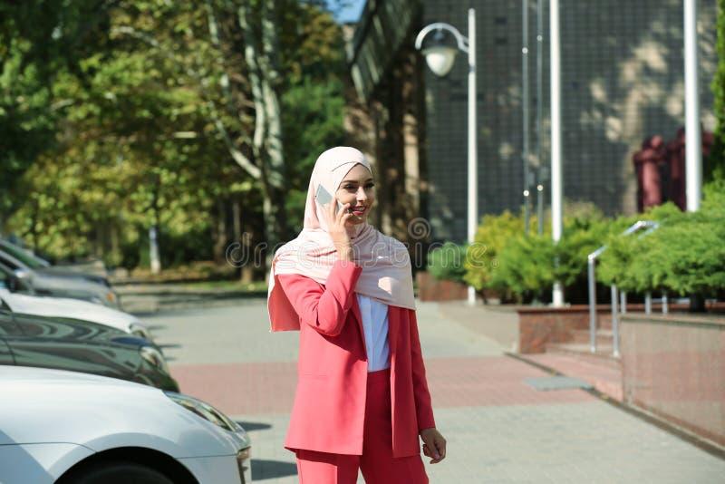 Muslim woman in hijab talking on phone. Outdoors stock photo