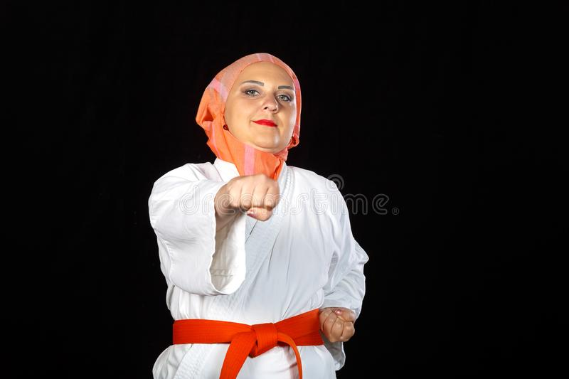 Muslim woman in kimono and hijab in a karate class is training with her hands. Horizontal photo stock image