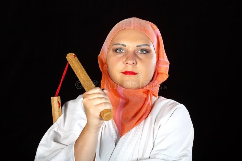 Muslim woman in kimono and hijab in karate class is training with nunchucks. Horizontal photo royalty free stock photo