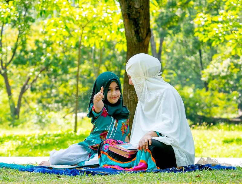 Muslim woman look at her child and girl show thumps up to the camera during reading some books in the garden stock photography