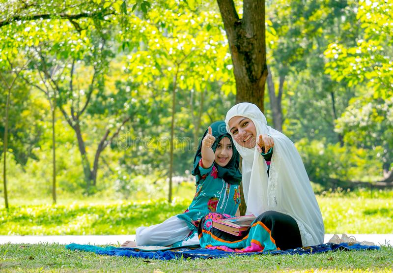 Muslim woman point to camera and girl show thumps up action during reading some books in the garden. Muslim women point to camera and girl show thumps up action royalty free stock image