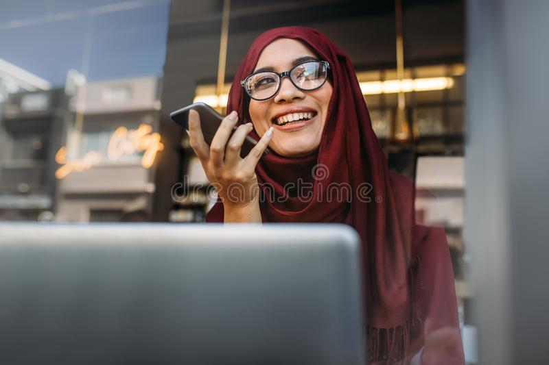Muslim woman running business online from coffee shop stock image
