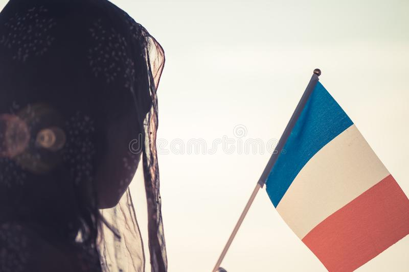 Muslim woman in scarf with French flag of at sunset.Concept. royalty free stock photos