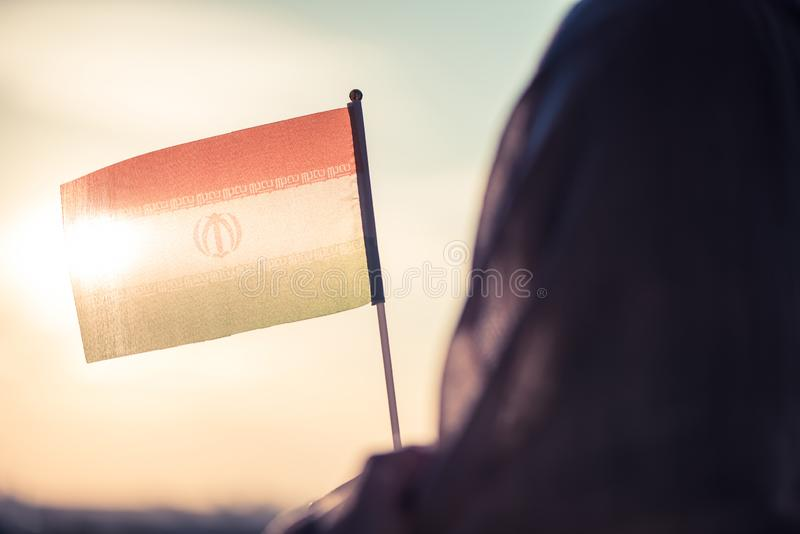 Muslim woman in scarf with Iranian flag at sunset.Concept. royalty free stock image