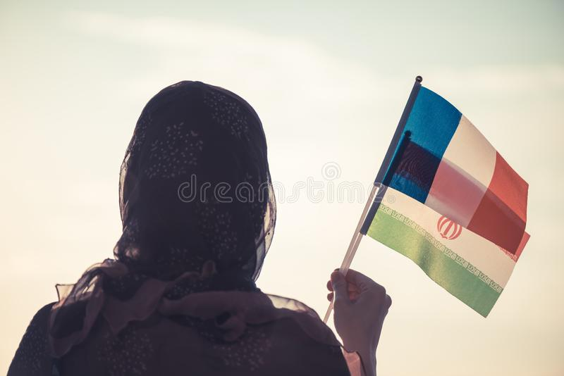 Muslim woman in scarf with  Iranian and French flags of at sunset.Concept. Muslim woman in scarf with  Iranian and French flags of at sunset.Concept royalty free stock photo
