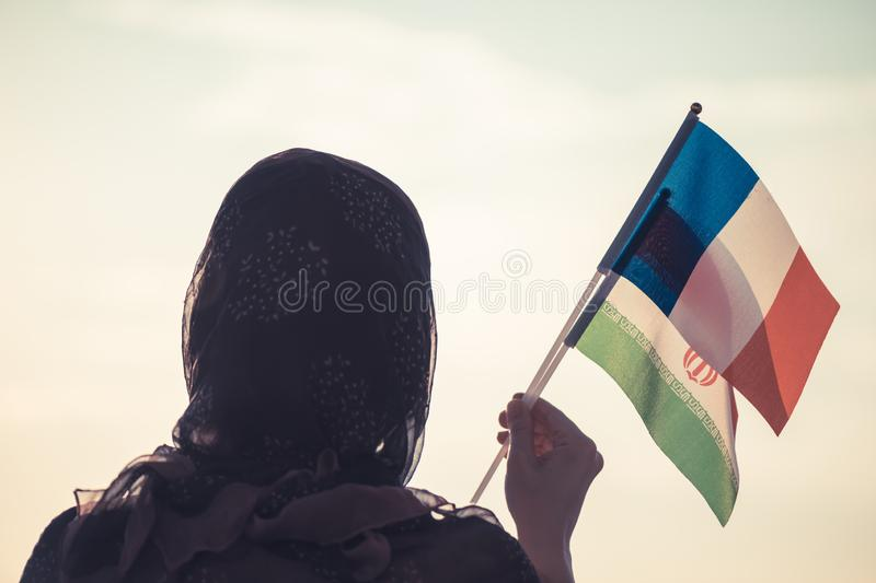 Muslim woman in scarf with  Iranian and French flags of at sunset. Concept royalty free stock photography