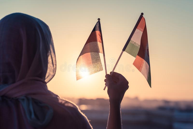 Muslim woman in scarf with Iranian and Germany flags of at sunset.Concept. Muslim woman in scarf with Iranian and Germany flags of at sunset.Concept royalty free stock images