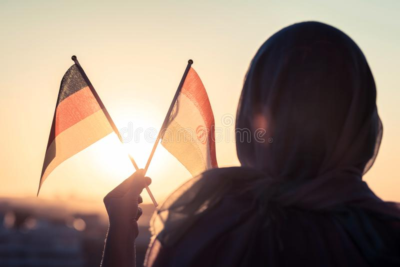Muslim woman in scarf with Iranian and Germany flags of at sunset.Concept. Muslim woman in scarf with Iranian and Germany flags of at sunset.Concept royalty free stock photos