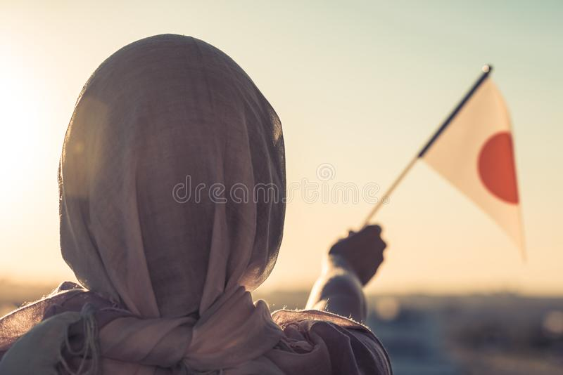 Muslim woman in scarf with Japanese flag of at sunset. Concept. royalty free stock image