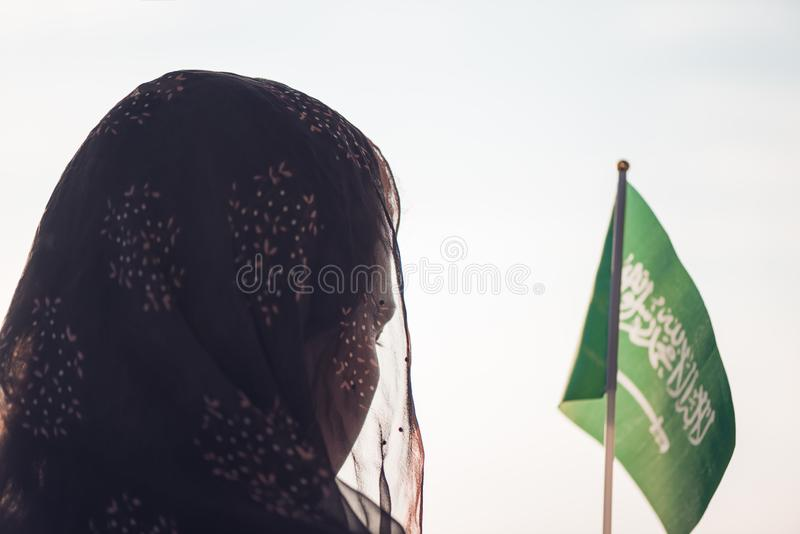 Muslim woman in scarf with Saudi Arabia flag of at sunset. royalty free stock photography
