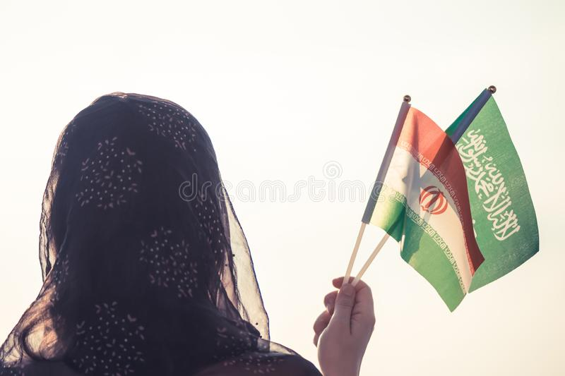 Muslim woman in scarf with Saudi Arabia and Iranian flags of at sunset background.Concept. Muslim woman in scarf with Saudi Arabia and Iranian flags of at stock image